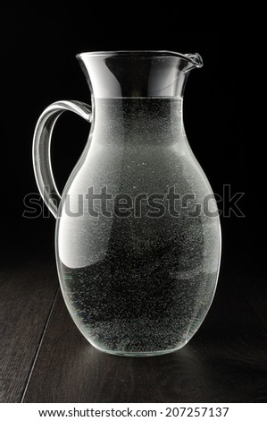 Pitcher full of drinking water on the dark background - stock photo