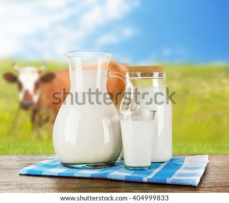 Pitcher, jar and glass of milk on wooden table against cow and blue sky background - stock photo