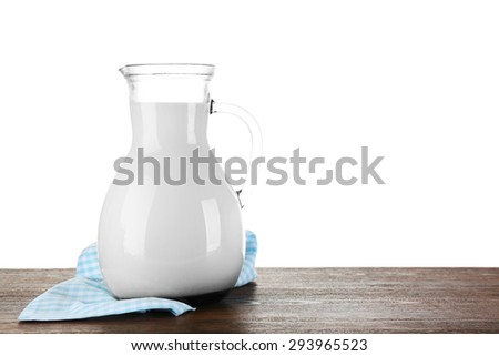 Pitcher of milk on wooden table, on white background - stock photo