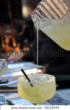 Pitcher pouring liquid into margarita glass. - stock photo