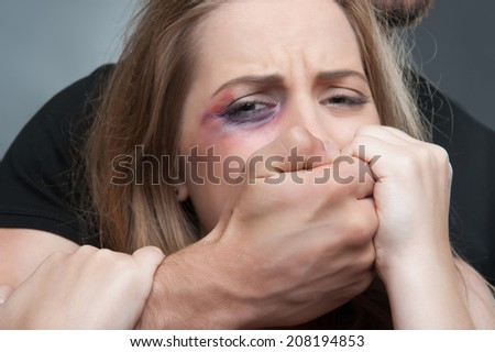 Pitiable scared young woman having black eye tearing herself away from her estranged husband standing behind her in black shirt. Isolated on grey background - stock photo