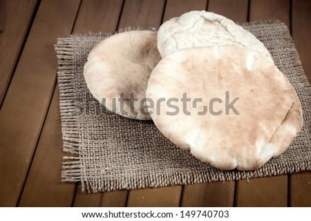 pitta bread (Lebanese Bread), over old burlap background - stock photo