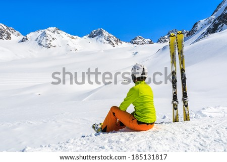 PITZTAL GLACIER, AUSTRIA - MAR 29: Young woman alpine skier sits in snow and looks at mountain peaks of Austrian Alps, Pitzta on 29th March 2014. - stock photo