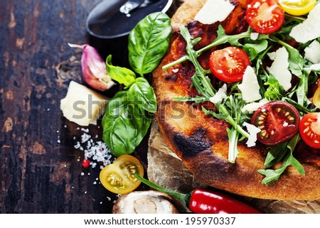 pizza and fresh italian ingredients on a dark background - stock photo