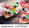 Pizza and slice of pizza in hand on the table - stock photo