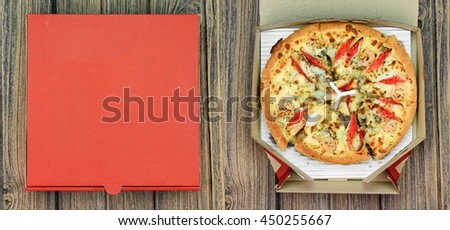 Pizza and the delivery box on wooden background, Fast food. - stock photo
