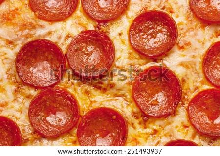Pizza background - macro shot of pepperoni pizza - stock photo