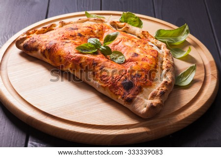 Pizza calzone with basil leaves close up - stock photo
