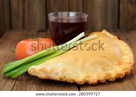 Pizza calzone with glass of red wine, fresh scallion and tomato - stock photo