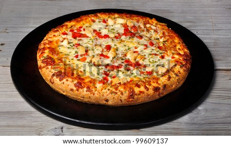 Pizza Chicken parmesan with tomato onion on old vintage wood table - stock photo