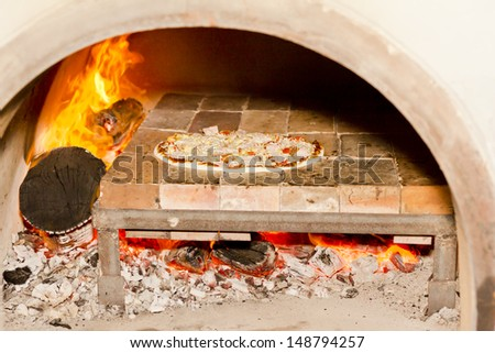 Pizza cooking in a tradition fire wood oven  - stock photo