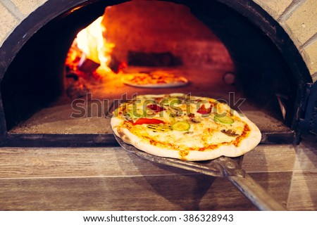 Pizza cooking in a traditional brick wood oven.Brick oven pizza on the wooden holder going to bake.Colorful vegetarian vegetable pizza baking  - stock photo