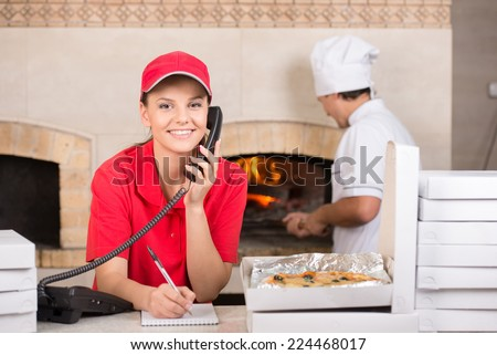 Pizza delivery service and chef in white  puts the pizza inside the wood oven to bake. - stock photo