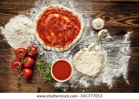 Pizza dough with ingredients on wood, shot from above - stock photo