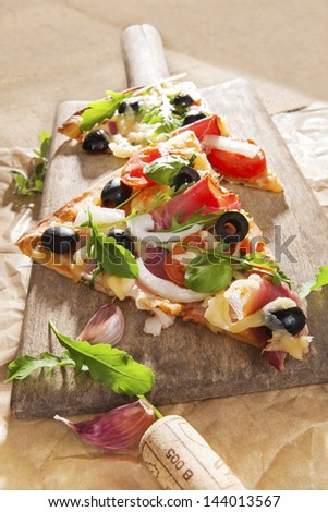 Pizza eating. Pizza piece with colorful toppings on wooden cutting board, with various ingredients, wine cork on brown background. Italian country style culinary kitchen. - stock photo