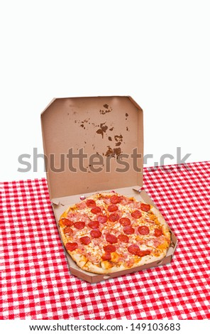 Pizza in a box. Tasty pizza with pepperoni sausage in white cardboard box on kitchen table - stock photo