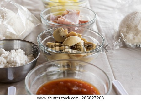 Pizza ingredient with mushroom ham pineapple dough and sauce on pink table - stock photo