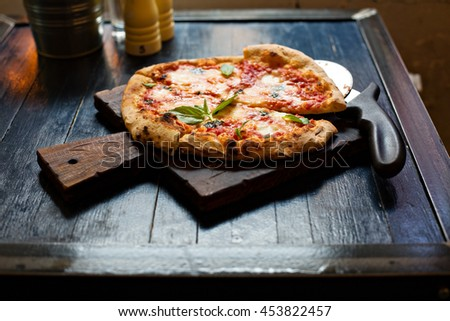 Pizza Margherita with mozzarella and fresh basil freshly baked on a table in cafe - stock photo