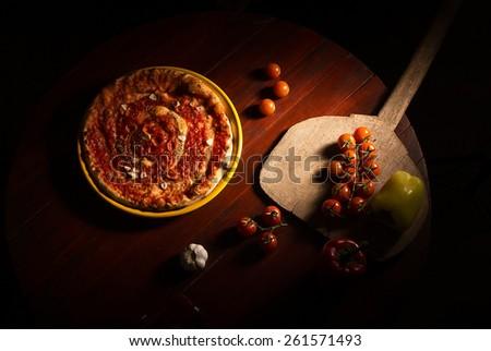 Pizza marinara with garlic on wooden table - stock photo