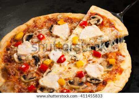 pizza on a dark background with ham, mushrooms, cheese and sweet pepper top view, cutting - stock photo