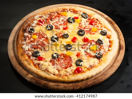 pizza on a dark background with ham, mushrooms, olives, cheese and sweet pepper top view - stock photo