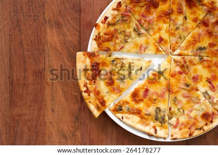 pizza on white plate on brown background - stock photo