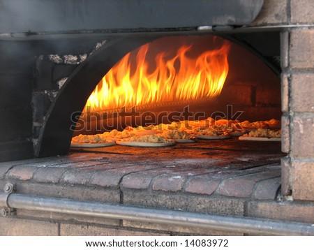 pizza prepares in old stove near fire - stock photo