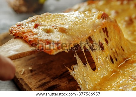 Pizza quattro fromaggi on a wooden board. Italian food. Man's hand takes a slice of fresh delicious pizza. - stock photo