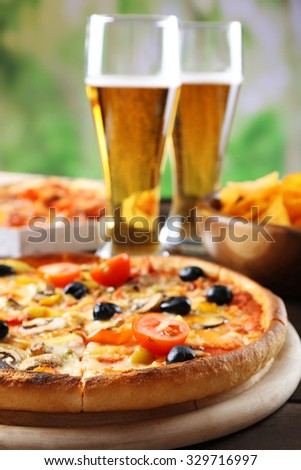 Pizza served with beer on wooden table - stock photo