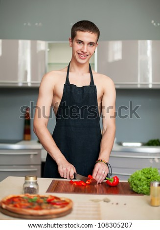 Pizza sexy chef prepares a pizza in the kitchen wearing an apron in the same - stock photo