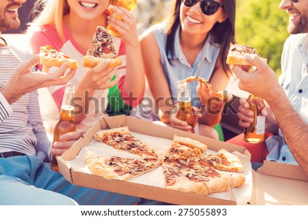 Pizza time! Close-up of four young cheerful people eating pizza and drinking beer outdoors - stock photo