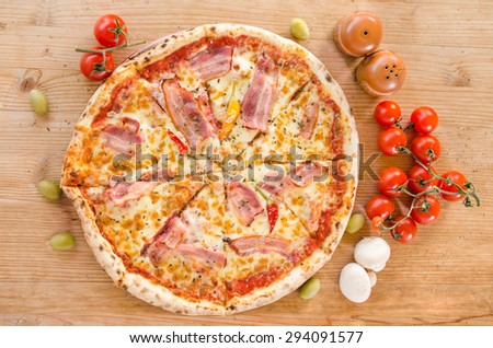 Pizza with bacon, pepperoni, melted cheese, olives , mushrooms and cherry tomatoes - stock photo
