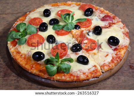 Pizza with cheese, a salami, tomatoes, olives and Rucola