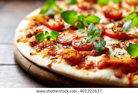 Pizza with cherry tomatoes with fresh oregano - stock photo