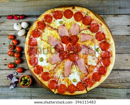 Pizza with decoration on a wooden board, pizza with sausage and ham,pizza no.01 - stock photo