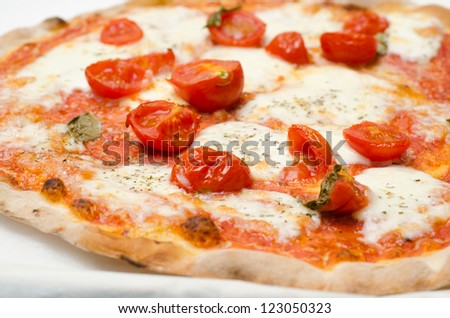 Pizza with fresh tomatoes, mozzarella and oregano - stock photo