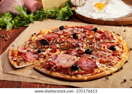 Pizza with Ham and Salami. Garnished with Olives - stock photo