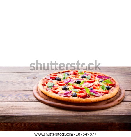 Pizza with ham, pepper and olives. Delicious fresh pizza served on wooden table. Pizza with tomato, salami and olives  Empty wooden tabletop  - stock photo
