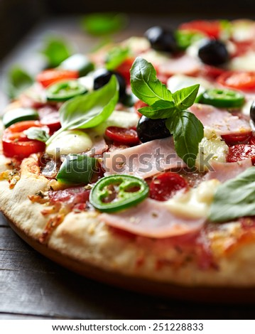 Pizza with ham, pepperoni, peppers and mozzarella - stock photo