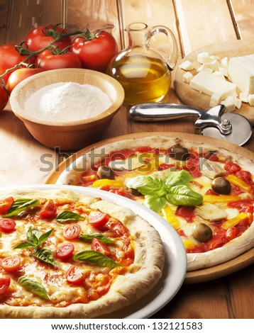 Pizza with ingredients on the wooden table - stock photo