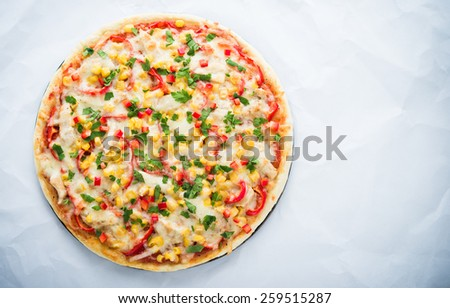 Pizza with mozzarella cheese, chicken, sweet corn, sweet pepper and parsley on white background top view. Italian cuisine. Space for text. - stock photo