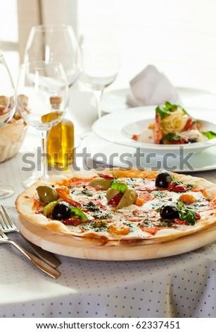 Pizza with Mozzarella Cheese, Fresh Tomato and Pesto Sauce. Served at Restaurant Table - stock photo