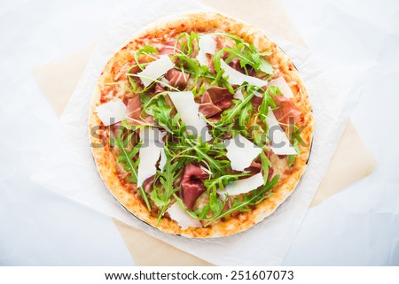 Pizza with prosciutto (parma ham), arugula (salad rocket) and parmesan top view. Italian cuisine. - stock photo