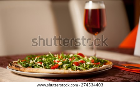 Pizza with rucola, cherry tomatoes and a glass of beer on a table of italian restaurant - stock photo