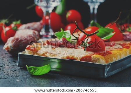 Pizza with salami and tomato, selective focus and toned image - stock photo