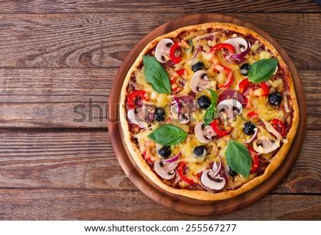 Pizza with salami, mushrooms, mozzarella and basil horizontal - stock photo