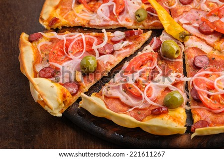Pizza with tomato, salami, peppeeoni, olives and yellow hot pepper - stock photo