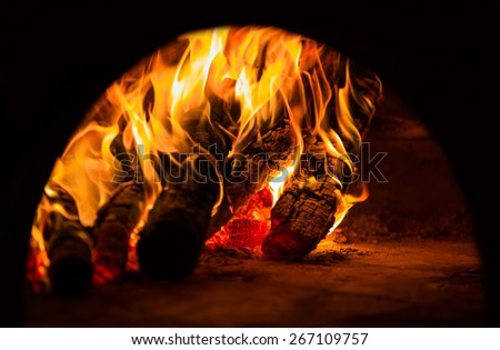 Pizzas baking in an open firewood oven  - stock photo