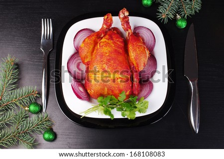 Place setting including one white dinner plate with grilled chicken on festive  black table - stock photo