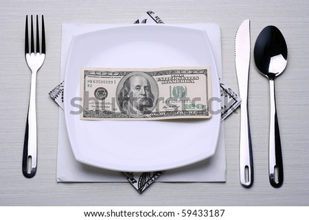 place setting including silverware and white plate filled with One Hundred Dollar Bill. - stock photo